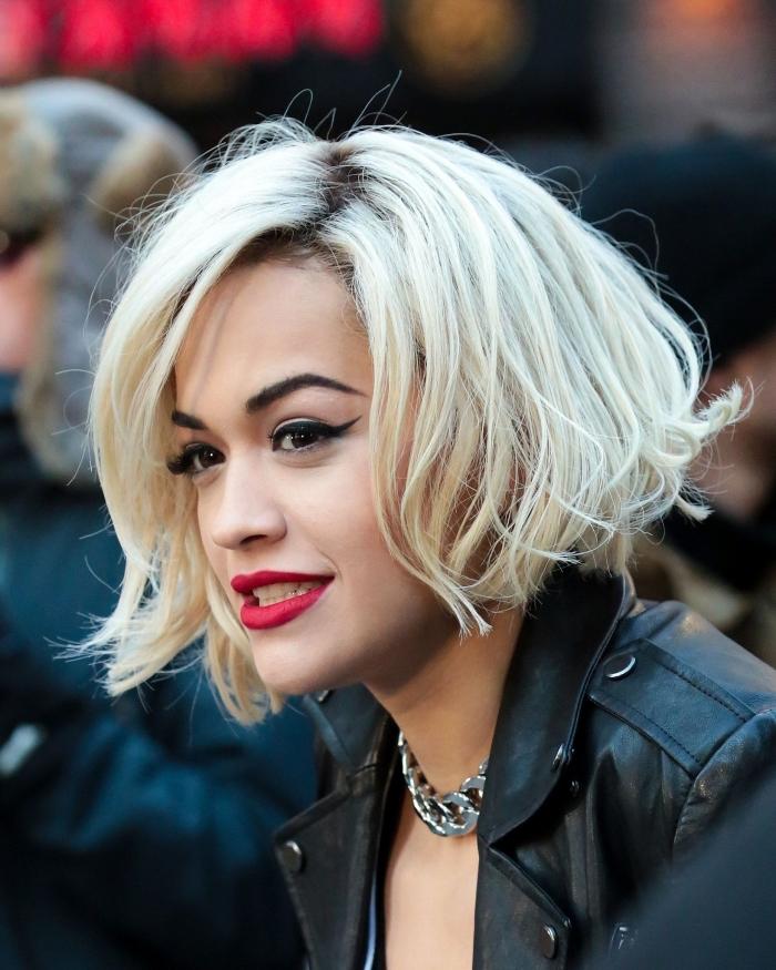Rita Ora avec coupe carré plongeant court aux racines foncées et pointes éclaircies en blond froid, maquillage avec rouge à lèvre rouge mate et eye liner