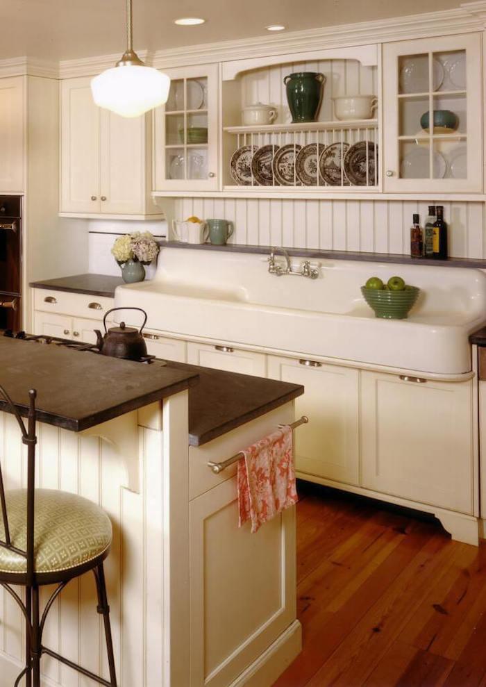 Vintage cuisine et lavabo, lampe originale, bol avec pommes vertes, vitrage pour disposer ses assiettes