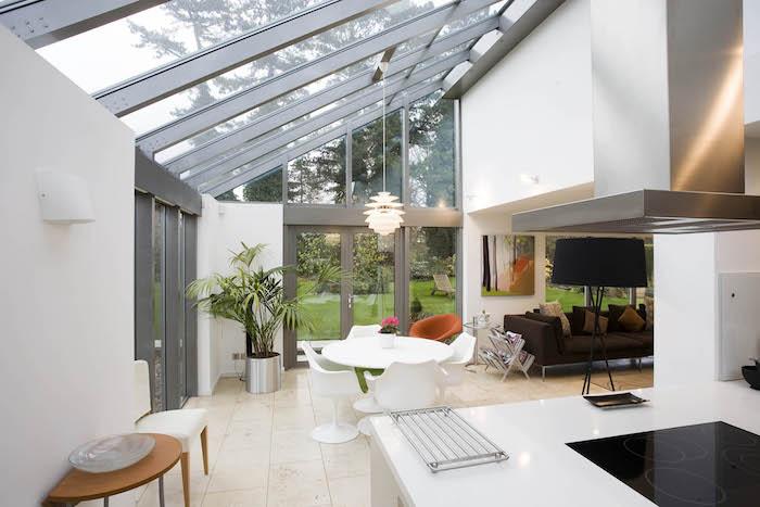 extension vitrée en prolongement d un salon blanc et gris pour abriter salle à manger à table ronde et chaises blanches et cuisine a coté