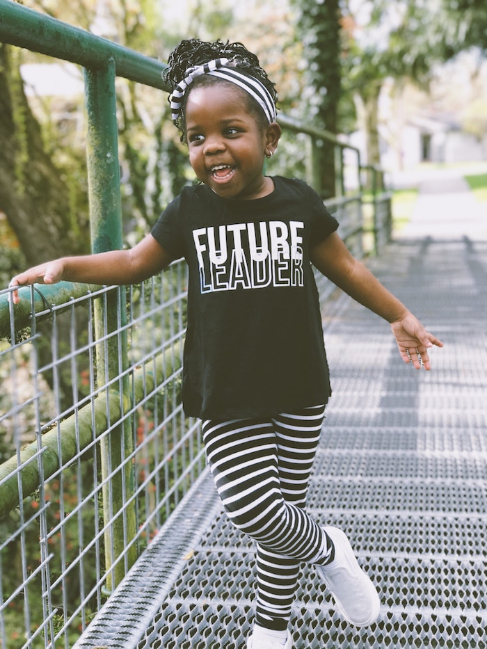 Adorable petite fille en tenue noir et blanc avec un bandeau de cheveux, coiffure simple en chignon cheveux crépus, fille souriante