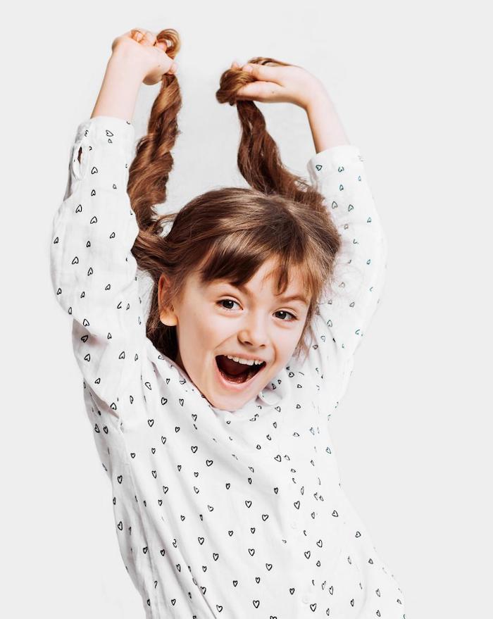 Deux tresses sur les cheveux longs de fille souriante en chemise blanche à coeurs, comment faire une coiffure pour fillette, tutoriel coiffure simple