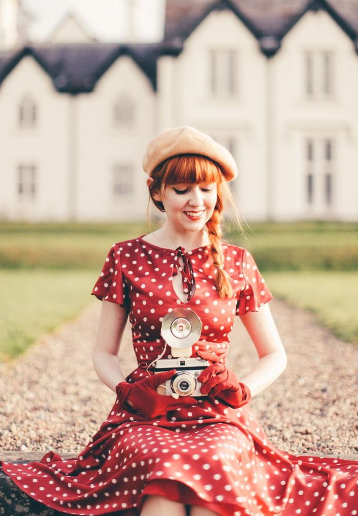 Femme en robe rouge à pois, soirée guinguette comment s'habiller, tenue rétro pour femme, appareil de photo vintage, cheveux roux en tresse