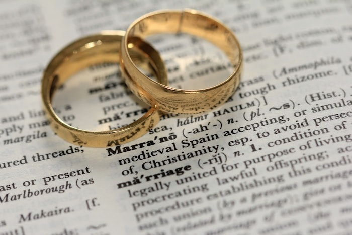 Alliances de mariage or jaune, photo romantique de deux alliances de meme style pour elle et lui sur un dictionnaire sur le mot mariage