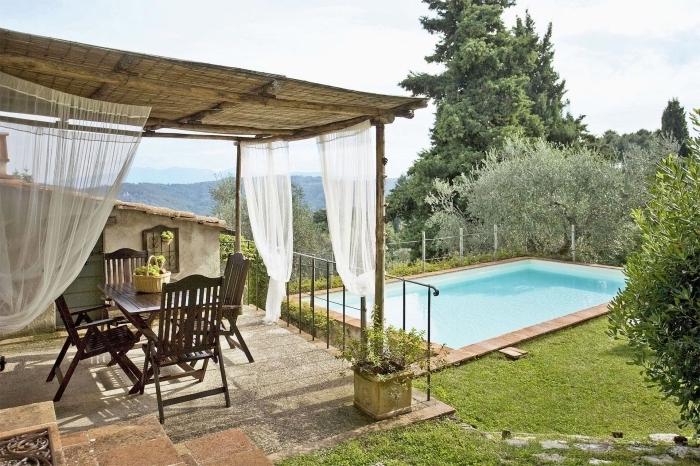 terrasse bétonnée avec toit en bambou et rideaux blancs aménagée avec meubles en bois foncé, amenagement autour piscine photos