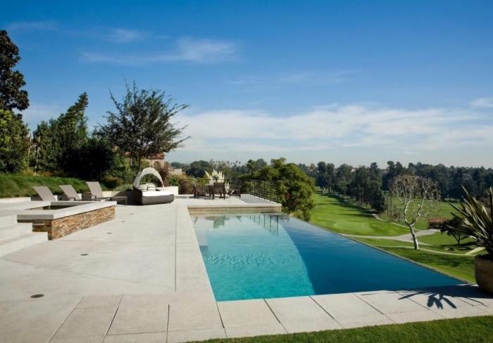 design minimaliste dans un jardin avec terrasse béton et grande piscine, meubles de jardin moderne à design tressé