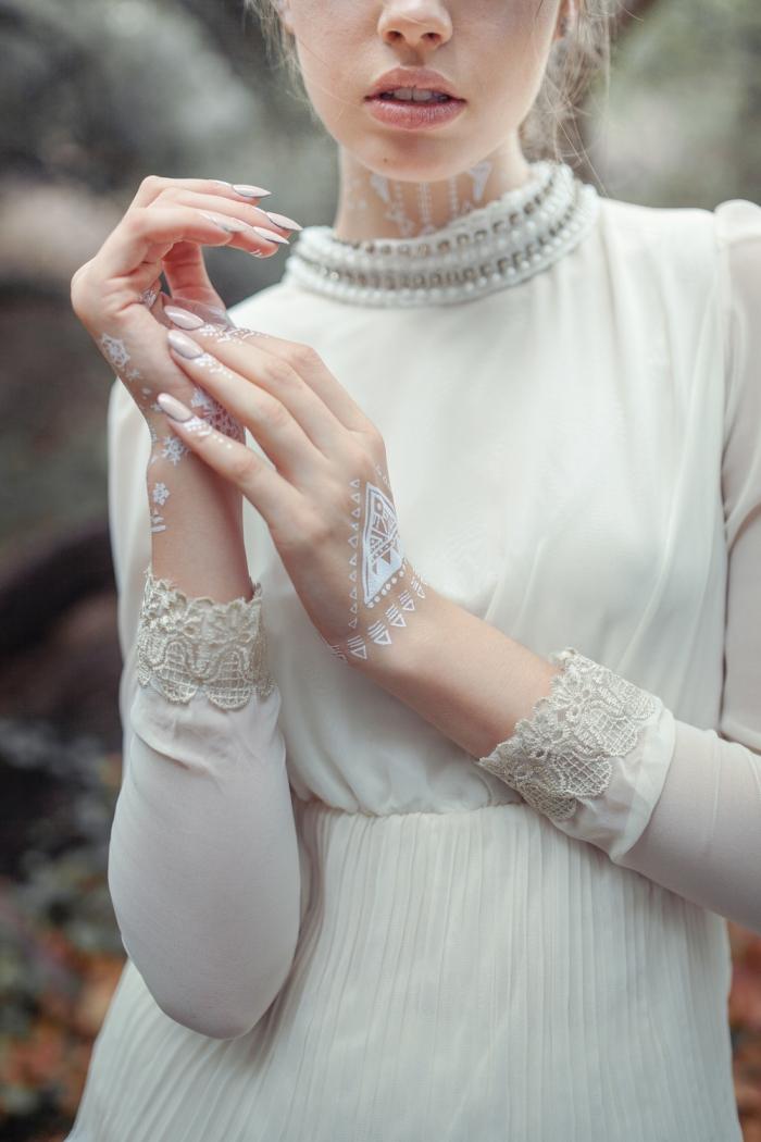 photo de henné en blanc sur la main aux motifs triangulaires, modèle robe de mariée blanche avec col perles