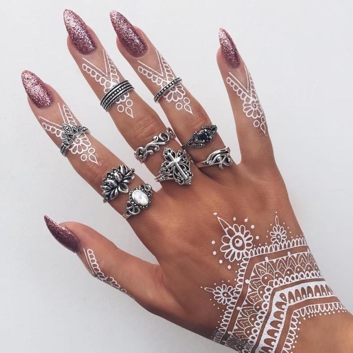 manucure ongles longs à vernis glitter rose, tatouage blanc temporaire sur main et doigts aux motifs ethniques