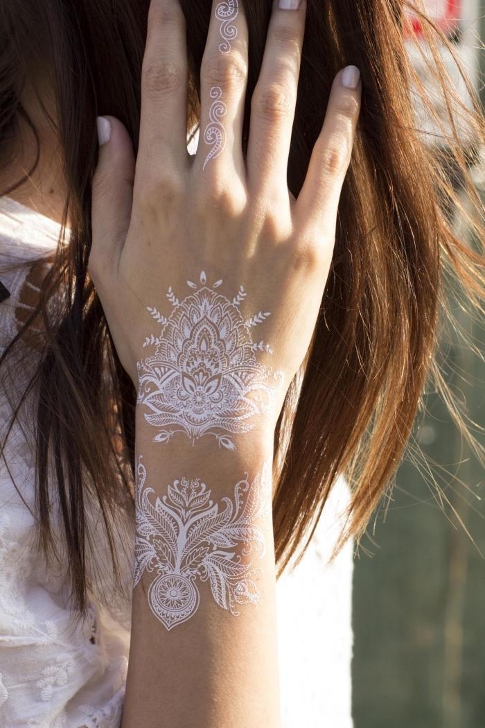 dessin main à motif henné, modèle de tatouage éphémère en blanc sur main et doigt, symbole tatouage henné