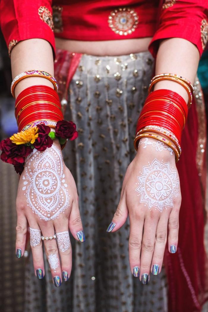 tatouage henné main symbolique, exemple comment décorer ses mains avec dessins blancs à effet bijoux mandala