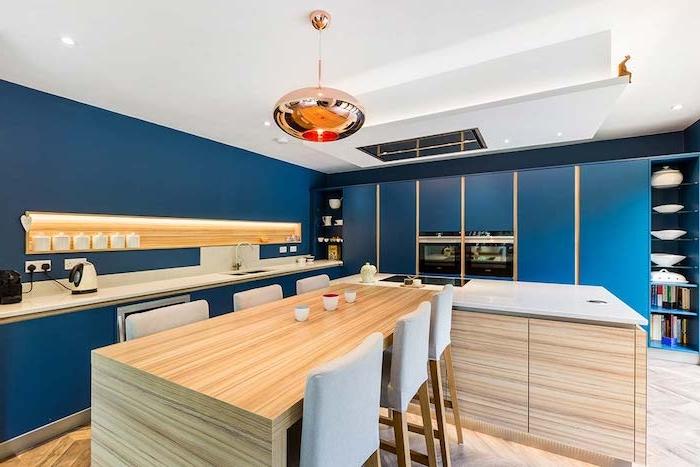 cuisine bleue outre mer avec des accents boisés introduits à travers un ilot central table bois, parquet bois clair, suspension cuivre