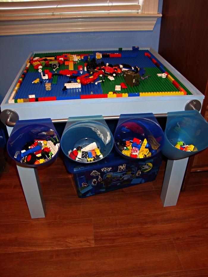 table pour lego avec barre métallique sur le côté et des bacs de rangement suspendus