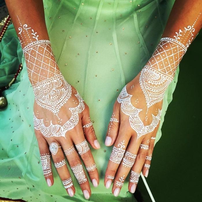 photo de henné sur main, modèle de tatouage temporaire sur mains aux motifs mandala, idée tattoo blanc temporaire