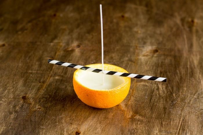 modèle petite bougie fait maison avec cire bougie fondue et versée dans une zeste d'orange, idée bougie facile à faire