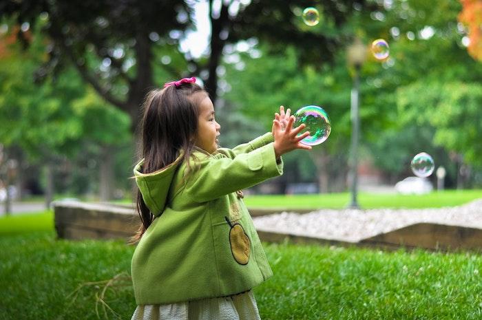 Petite fille qui joue avec ballons de savon, coiffure petite fille, coiffure tresse, tuto coiffure facile, manteau vert, printemps jardin vert