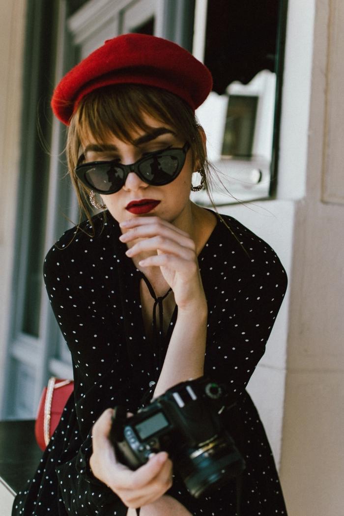 Belle fille coiffure avec frange, lunettes de soleil noires, béret rouge, appareil de photo, tenue guinguette, soirée guinguette comment s'habiller