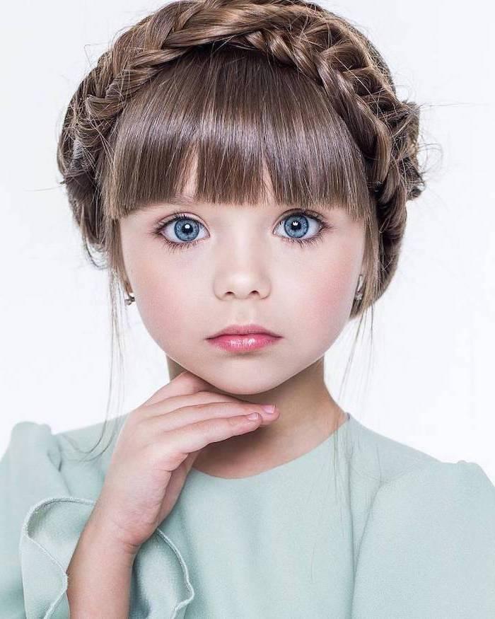 Tresse couronne sur cheveux longs coupe avec frange, fillette yeux bleus et robe bleue adorable, coiffure enfant, coiffure tresse, comment se coiffer