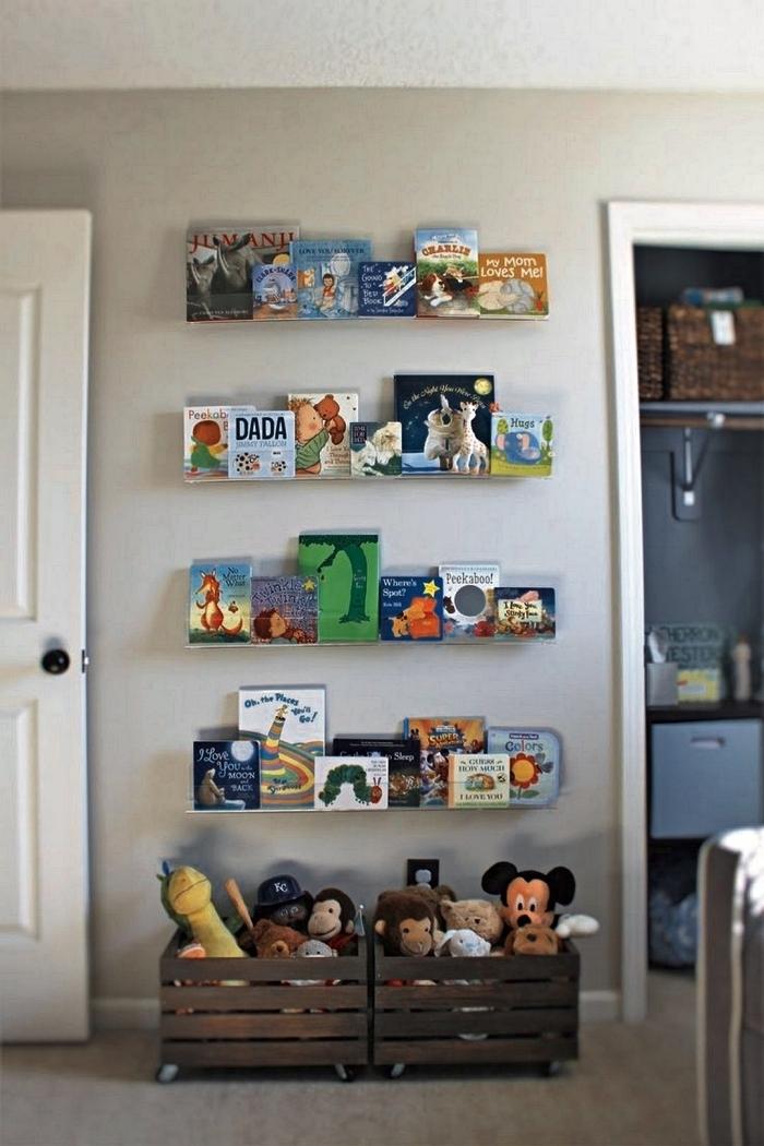 étagères murales pour y mettre en avant les livres d'enfants et des caisses de rangement vintage en bois pour ranger les peluches