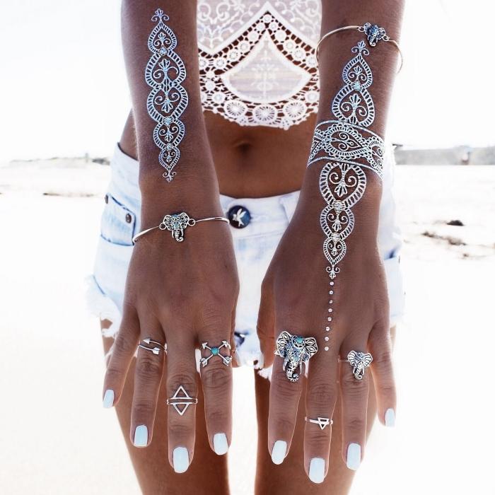 idée tattoo effet henné blanc autocollant, exemple de tatouage bohème sur les mains aux motifs ethniques et mandala