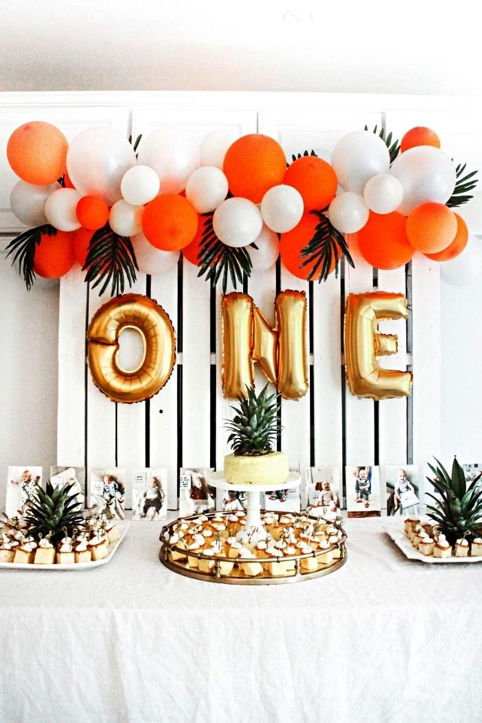 idée déco anniversaire pour réaliser un joli buffet gourmand, candy bar d'anniversaire 1 an décoré d'une palette récup et d'une guirlande ballons bi-colore en toile de fond