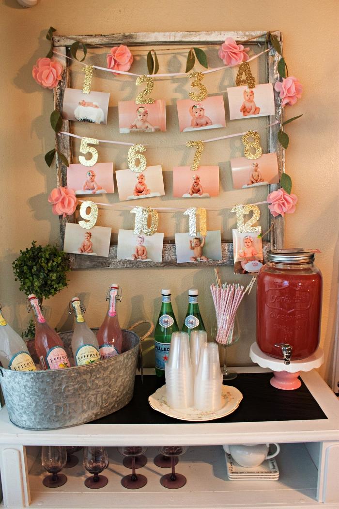 idée decoration anniversaire bébé 1 an, porte-photos en bois récup décorée d'une guirlande de roses en papier comme déco murale du bar à boissons