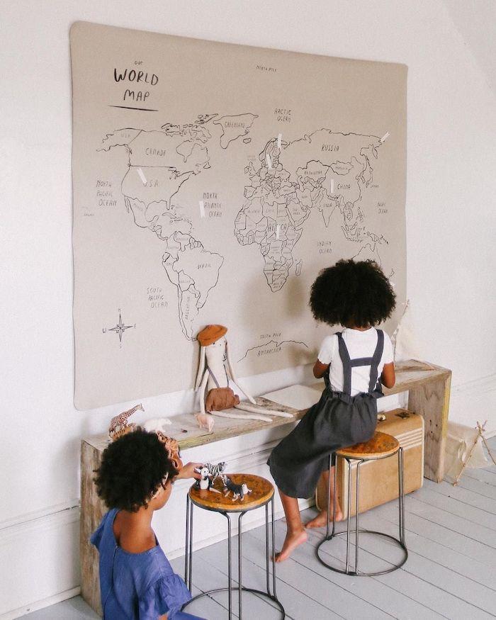 Enfants mignons qui jouent dans leurs chambre avec petit coin bureau diy de banc en bois, plan du monde gris dessiné par eux a feutre noir