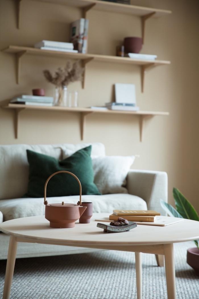 design salon aux murs de peinture beige sable avec meubles en bois clair, objets décoratifs de nuances de vert