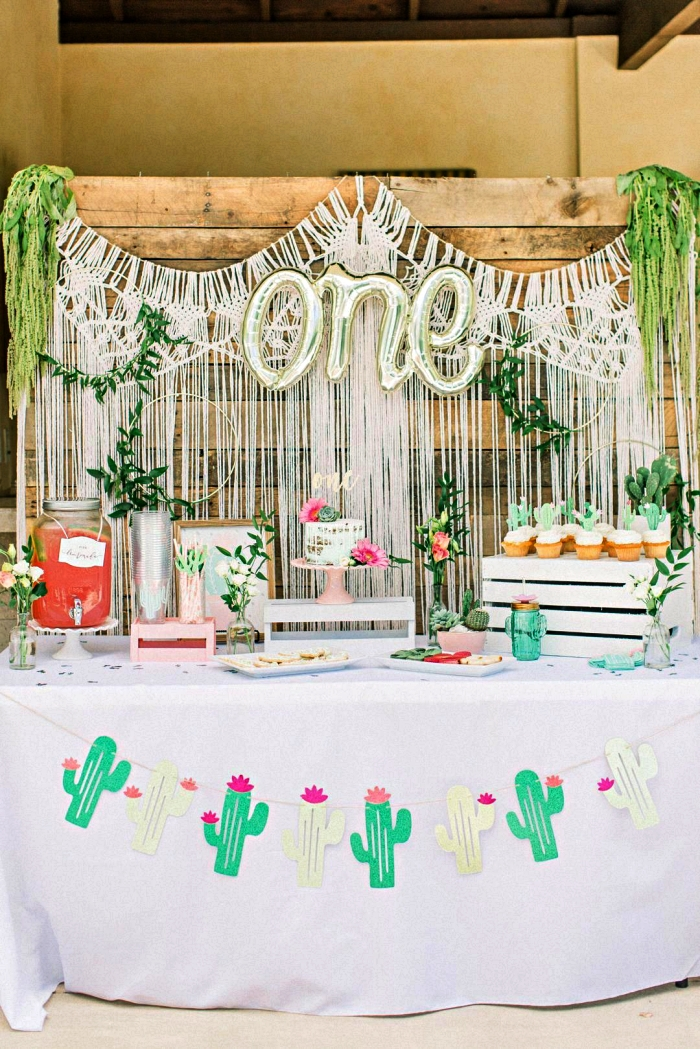 anniversaire 1 an bohème chic, candy bar d'anniversaire 1 an décoré d'une guirlande cactus, d'un rideau bohème chic en toile de fond, deco anniversaire enfant bohème chic