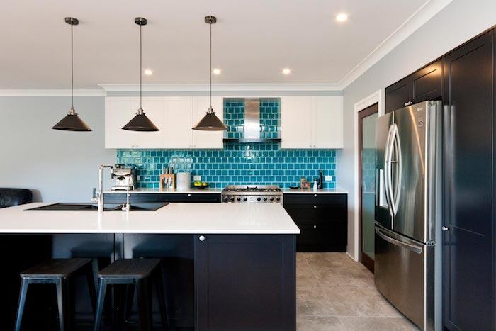 modele de cuisine noir et blanc avec une credence turquoise, meuble bas et ilot central noir, sol carrelage effet beton
