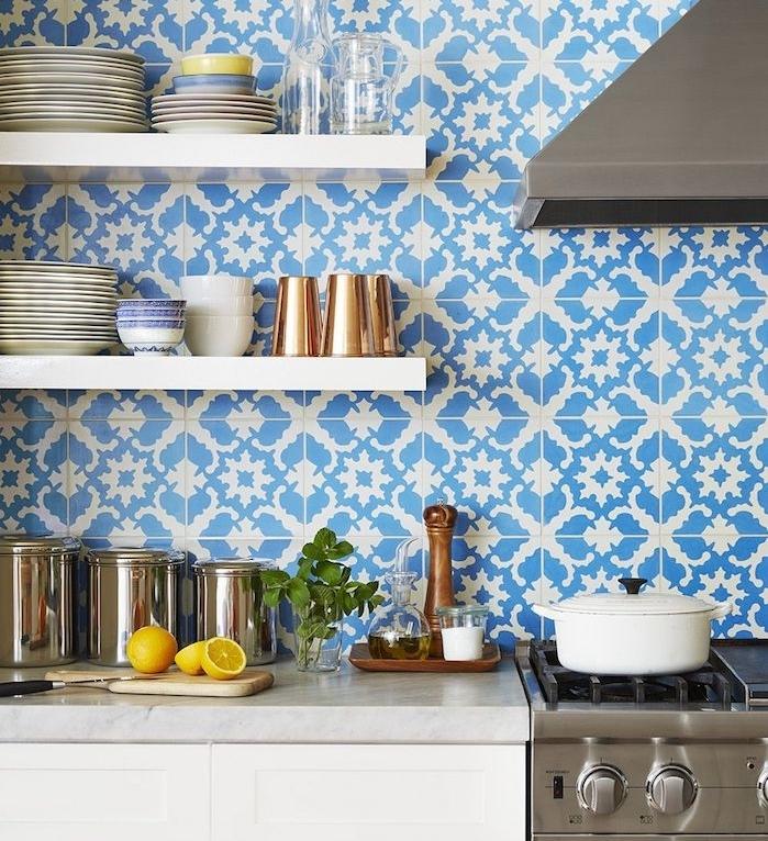credence carrelage mosaique bleu et blanc comme fond d étagères blanches surchargées de vaisselle, electromenager inox