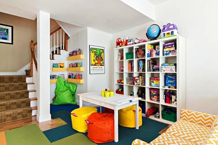 aménagement d'un coin de jeu avec un meuble caisson, des étagères murales, table et poufs