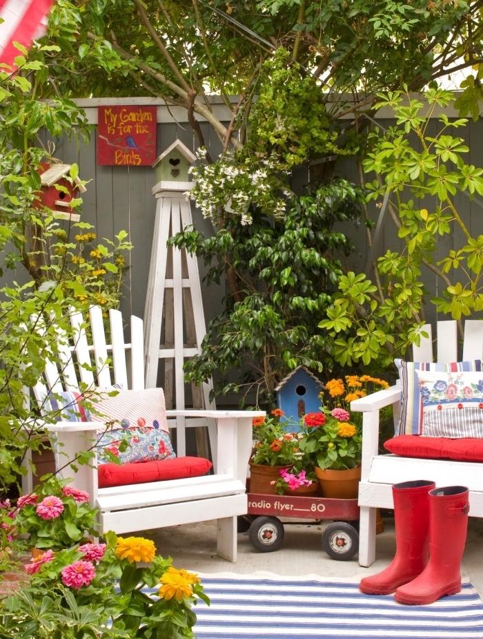 comment aménager son jardin, cour arrière à espace limité avec clôture bois et meubles en bois blanc décoré avec accessoires rouges