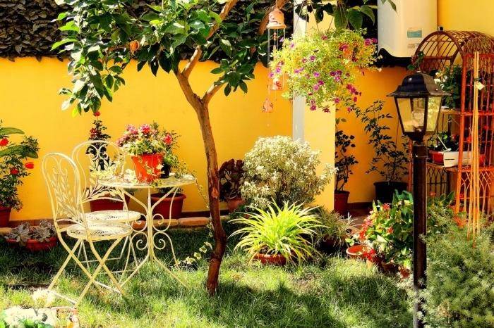 design extérieur de style vintage avec chaises et table en fer forgé, aménagement petit espace extérieur avec accessoires en métal