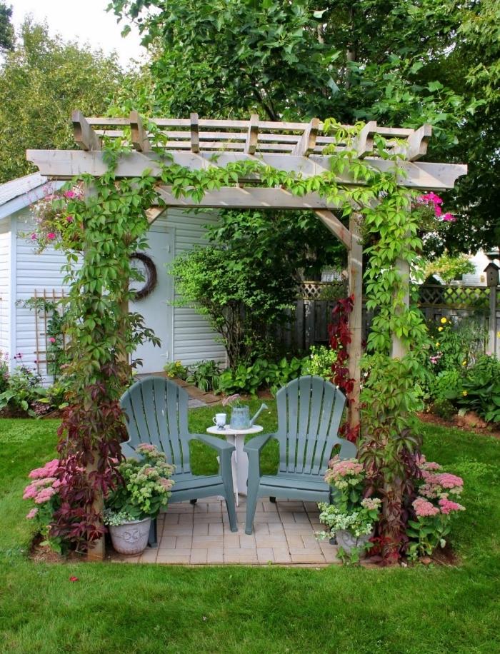 amenagement jardin paysager dans une cour arrière, déco arc en bois avec chaises grises et petite table ronde