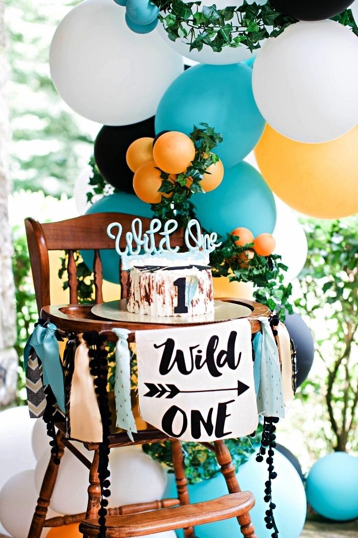 idée déco anniversaire 1 an sur le thème forêt, chaise haute bébé décorée d'une guirlande tassels et de ballons