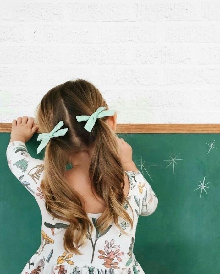 Fillette coiffure mignonne avec rubans vert ment claire, fille qui dessin sur une surface ardoise verte