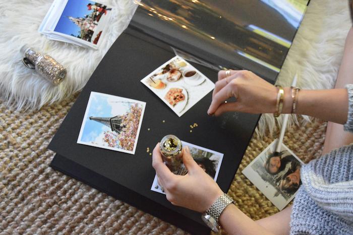 Papier en carton noir, photographies de voyage à Paris, femme qui met de brillants autour les photos, album scrapbooking, comment faire soi meme un scrapbooking voyage