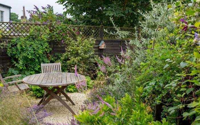 exemple de petit jardin avec galets et plantes vertes aménagé avec coin de repos en table et chaises pliantes bois