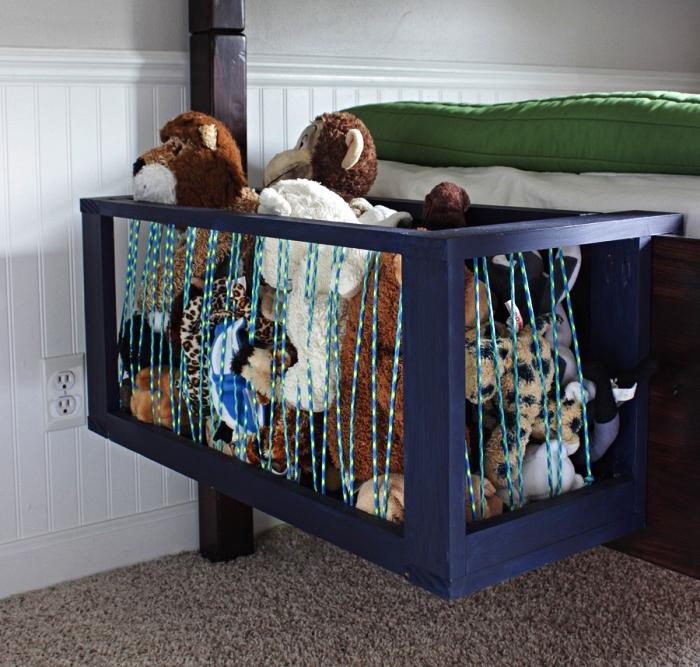une cage à peluches avec de la corde élastique fixée sur le côté du lit dans la chambre d'enfant, coffre a jouet pour ranger les peluches