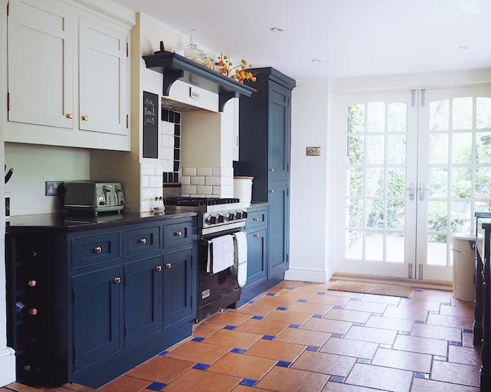 mobilier de cuisine bas bleu marine foncé et mobilier haut blanc, carrelage sol orange et bleu