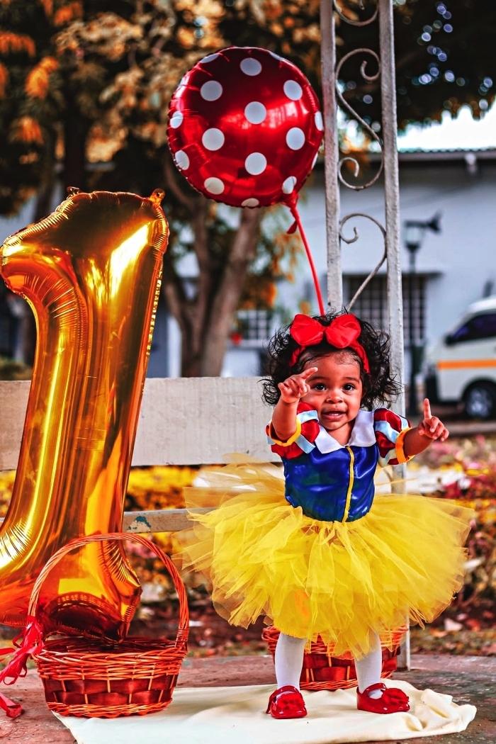 costume d'anniversaire blanche neige, ballon chiffre en aluminium et ballon mylar à pois pour une séance photo premier anniversaire