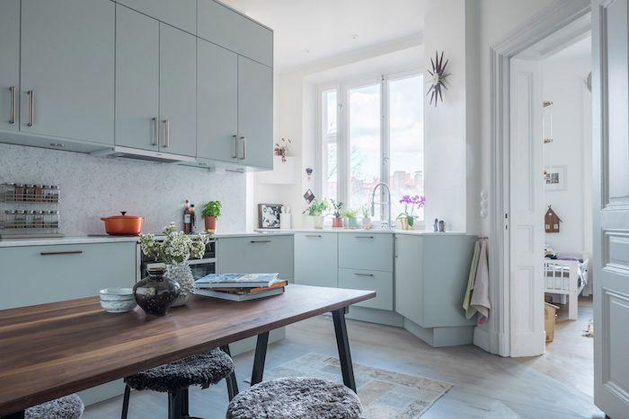 modele cuisine grise et blanche, nuance bleu gris clair pour la facade cuisine, table salle à manger bois et metal. tabouret habillé de coussin d assise moelleux, murs blancs