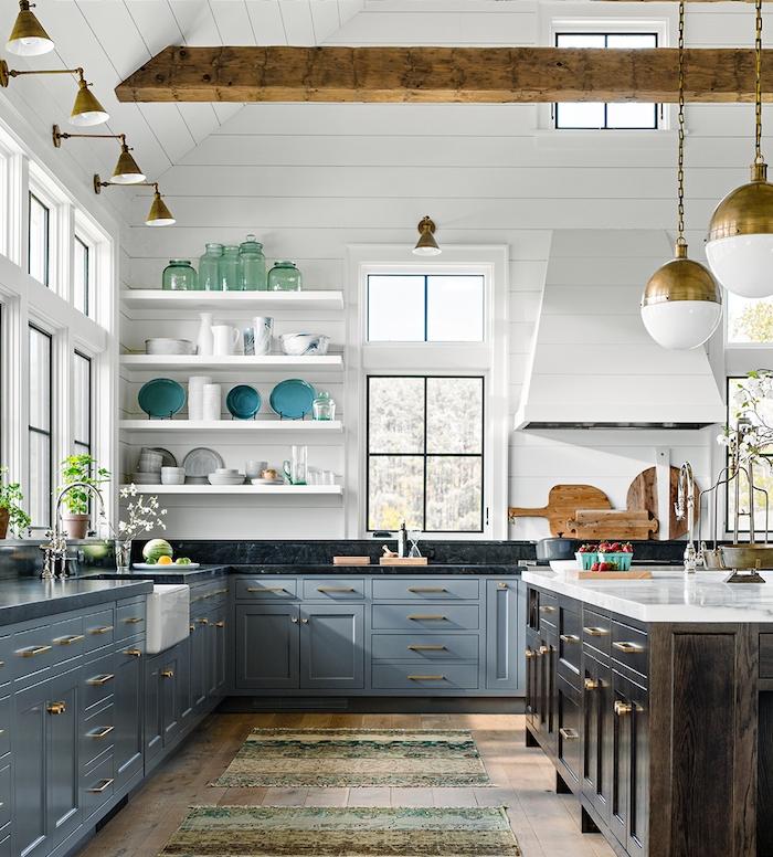 poutre apparente pour decorer un une cuisine grise et bois, facade cuisine bleu gris, parquet bois, murs lambris blanc, ilot central bois, plan de travail marbre noir, étagères blanches surchargées de vaisselle