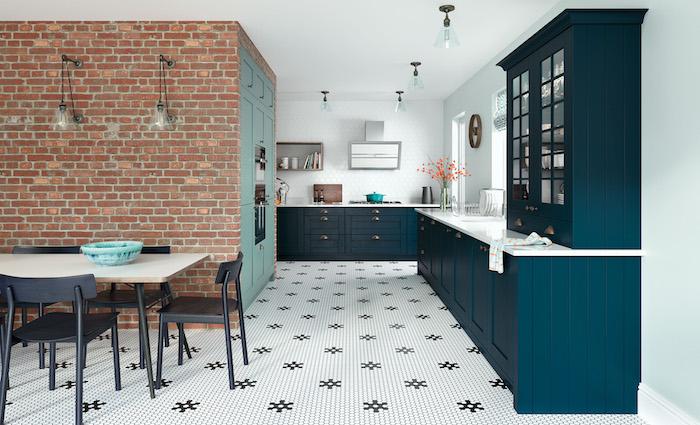 modele de cuisine industrielle avec mur de briques, meuble cuisine bleu petrole, sol carrelage blanc et noir à motif fleur, table salle à manger bois et chaises noires industrielles