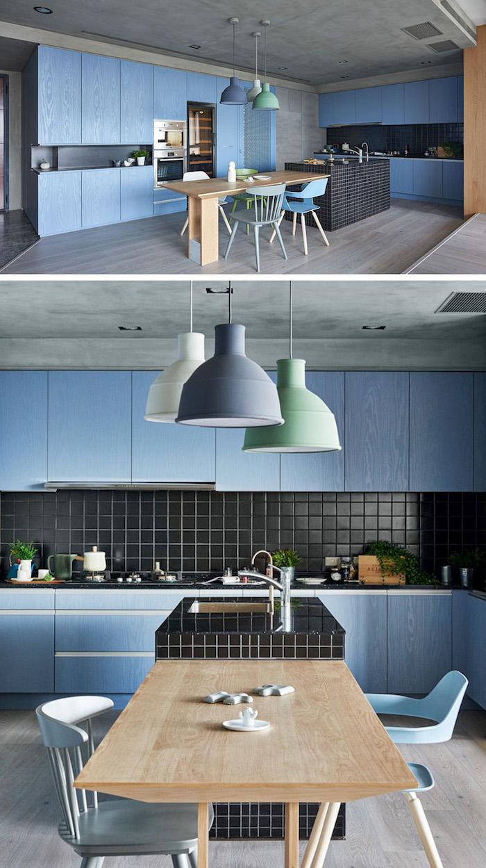 camaieu de bleus pour la deco cuisine avec credence carrelage noir, facade cuisine bleu intense, suspensions originales, ilot central noir, chaises bleu pastel