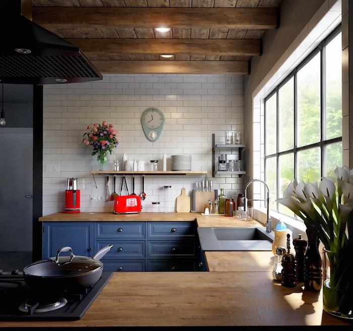repeindre meuble cuisine de couleur bleu nuit, mur carrelage blanc, plan de travail bois, poutres apparentes et plafond bois, deco campagne de cuisine