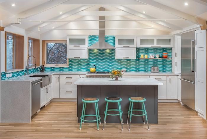 credence turquoise dans une cuisine blanche et grise avec ilot gris, parquet bois, facade blanche, ossature apparente