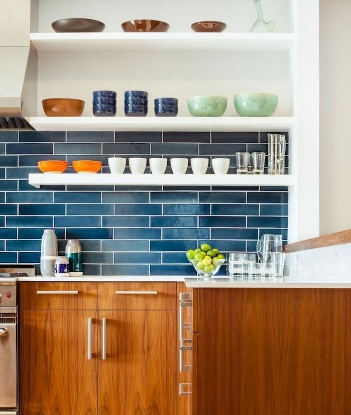 cuisine bleu, bois et blanc avec des étagères blanches surchargées de vaisselle et meuble bas bois