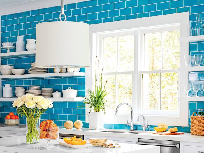 modele de cuisine bord de mer avec credence carrelage turquoise, étagères blanches surchargées de vaisselle blanc et verre, ilot central blanc