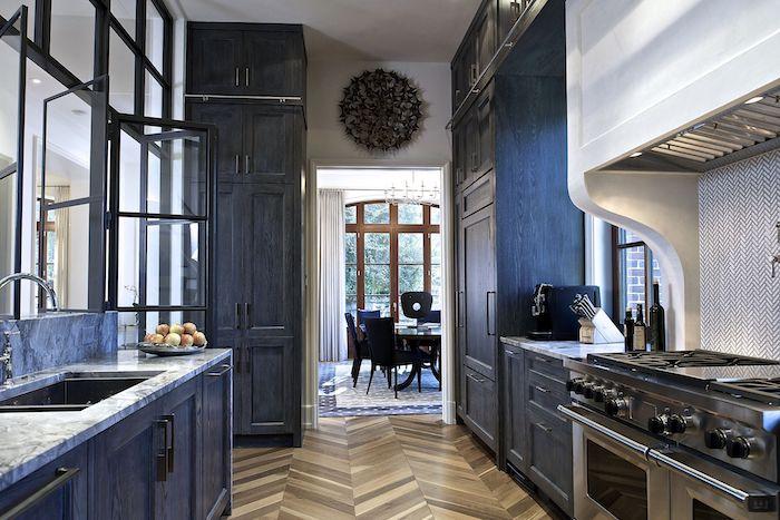 meuble cuisine bleu marine, modele armoire de cuisine haute, electromenager inox, parquet bois, plan de travail marbre et verriere de cuisine