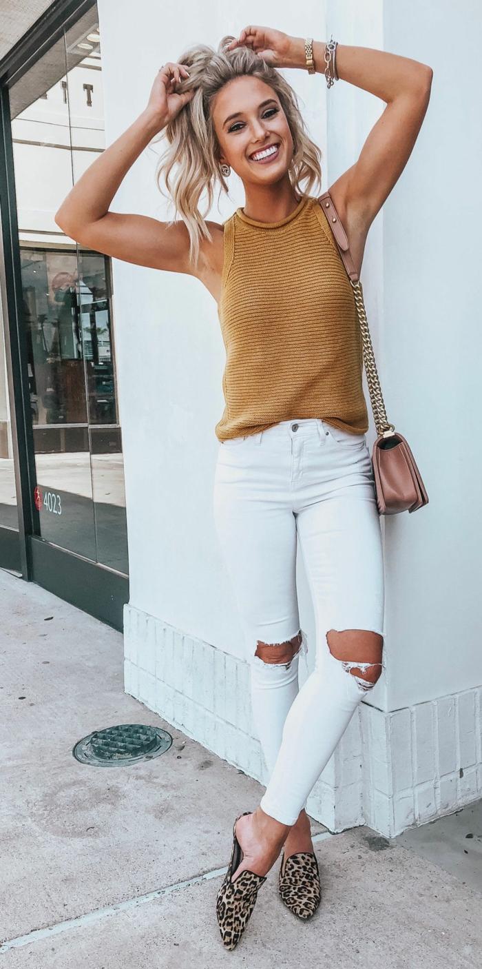 Femme souriante habillée bien en jean blanc déchiré et haute sans manches, tenue d'été décontractée chic, tenue tendance style chic femme